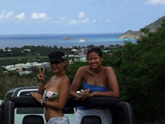 Kammi and Becky pose atop the rental jeep with the French side of St Martin in the background