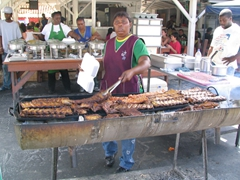 A chef prepares some spicy ribs for the BBQ grill; Grand Case