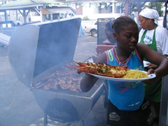 A waitress delivering freshly grilled lobster for a hungry customer; Grand Case