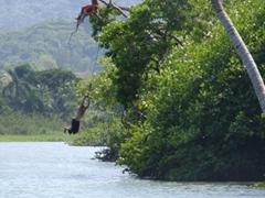Local boys having a blast swinging into the river; Rio Grande
