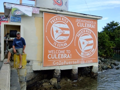 "Robby sitting beside the ""Welcome to Culebra"" sign; Dewey"