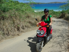 Becky zooming on the scooter; road leading away from Zoni Beach on Culebra