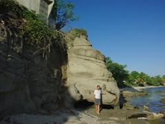 Becky stands beside a massive rock lining Esperanza's beach; Vieques