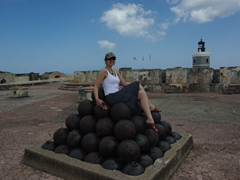 Becky atop a pyramid of cannon balls; El Morro Fortress