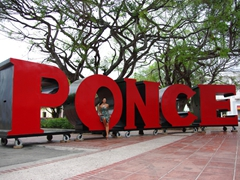 Becky sits in a massive Ponce sign