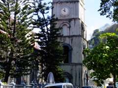 Uniformed school girl crossing the street in front of the main tower of the Cathedral of Immaculate Conception; Castries