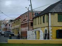 This yellow-sided building with a cedar-capped roof was built as the Old Scalehouse in 1856. All taxable goods leaving and entering Christiansted's harbor were weighed and inspected here. The old scales are still there