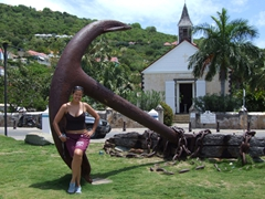 Becky is dwarfed beside the anchor; an Anglican church is in the background