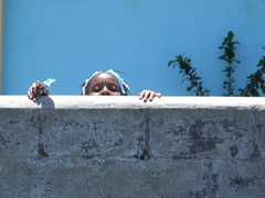 Nevian school girl peeking over the top of the wall