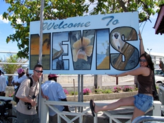 "Robby & Franny pose in front of the ""Welcome to Nevis"" sign"
