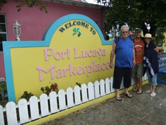"Bill, Robby and Laverne beside the ""Welcome to Port Lucaya Marketplace"" sign"