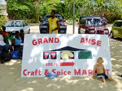 Cute kid playing in front of the Grand Anse Craft & Spice market sign