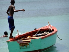 Local boy about to leap backwards off a colorful fishing boat; Grande Anse Beach