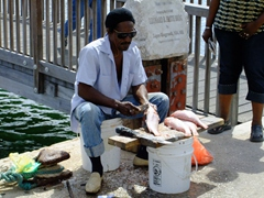 Man descaling fish by the curb side; Punda