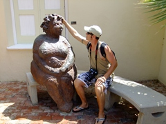 Robby sits beside a statue at the very excellent Kura Hulanda Museum