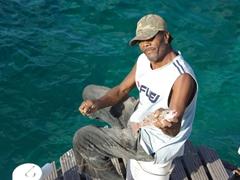 Fisherman showing off his fresh catch; Queen Emma Floating Bridge