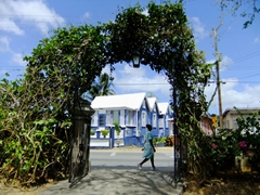 A Barbadian woman strolls by a natural arch; Chattel houses in the background