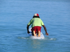 Surfer boy paddling amid calm waters
