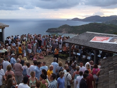 Crowds of tourists gather to listen to a steel band's live music at Shirley Heights, a Sunday tradition