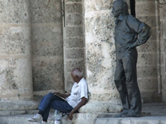 A local leans against a column while a statue stares over his shoulder; Plaza de la Cathedral