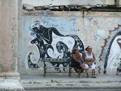 Ladies sitting in front of a graffiti painted wall; Havana