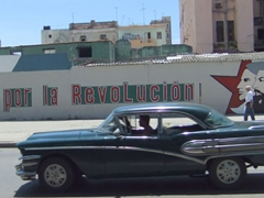 "A vintage car whizzes by a common city slogan ""todo por la revolucion"""