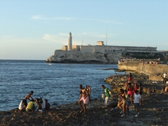 Families enjoying the vista from the malecon with El Morro in the background