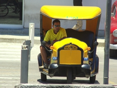 A three wheeled taxi awaits his next passengers