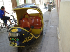 Coco taxis are everywhere in Havana, waiting to take their passengers on a precarious ride through town