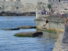 Caught in mid-air, a boy leaps into the refreshing water by the malecon