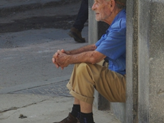 Resting in his doorway, an elderly Cuban man watches the hustle and bustle of busy Havana