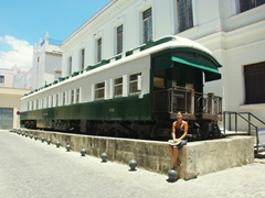 Becky poses beside Coche Mambi (a 1900 train car built in the US, and brought to Cuba in 1912 as the Presidential car, a palace on wheels with a formal dining room)