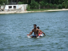 Two locals use a makeshift raft to float from Cayo Granma over to La Socapa