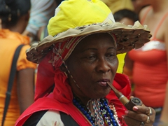 A lady looks deep in thought while puffing on a pipe; Fiesta del Fuego
