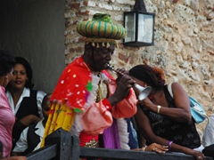 A colorful musician blows his horn; Fiesta del Fuego at El Morro