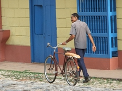 A man walks beside his bread strapped to his bike; Trinidad's colonial section