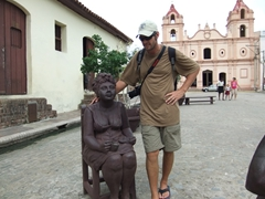 Robby strikes a pose next to a seated sculpture with the Iglesia de Nustestra Senoria del Carmen in the background