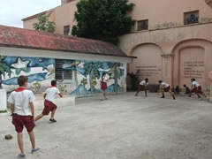 School kids playing a modified game of baseball; near Plaza del Carmen