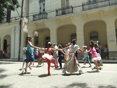 Young girls sing and dance in front of the Bayamo Ayuntamiento (city hall)