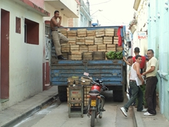 A truck filled with produce barely fits down a narrow street in Bayamo