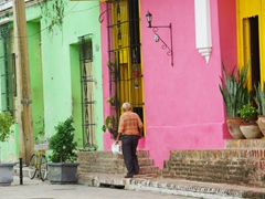 An old man passes by the colorfully restored buildings of Plaza San Juan de Dios