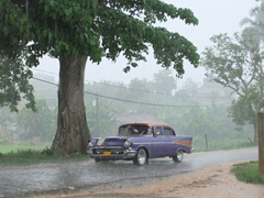 A classic automobile slowly creeps down a flooded road in Vinales