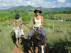 Fidel and Becky riding through the countryside; Vinales