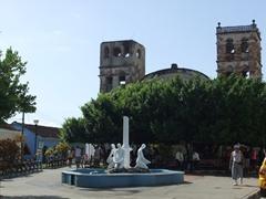 The towers of the Catedral de Nuestra Senora de la Asuncion are barely visible from Baracoa's main plaza