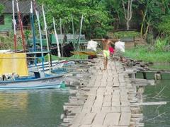 Boy balancing goods across the bridge