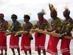 Red sarong men perform on the beach at the Hiri Moale Festival