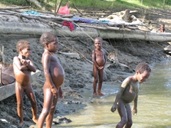 Naked children play by the riverside