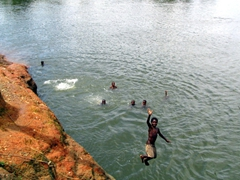 Children showing off as they plunge off the cliff into the river