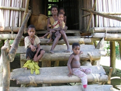 Villagers sitting outside their home; village along the Sepik River