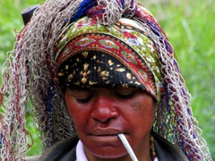 Lady from Tari with a bilum bag full of market items (draped from her head) takes a smoke break